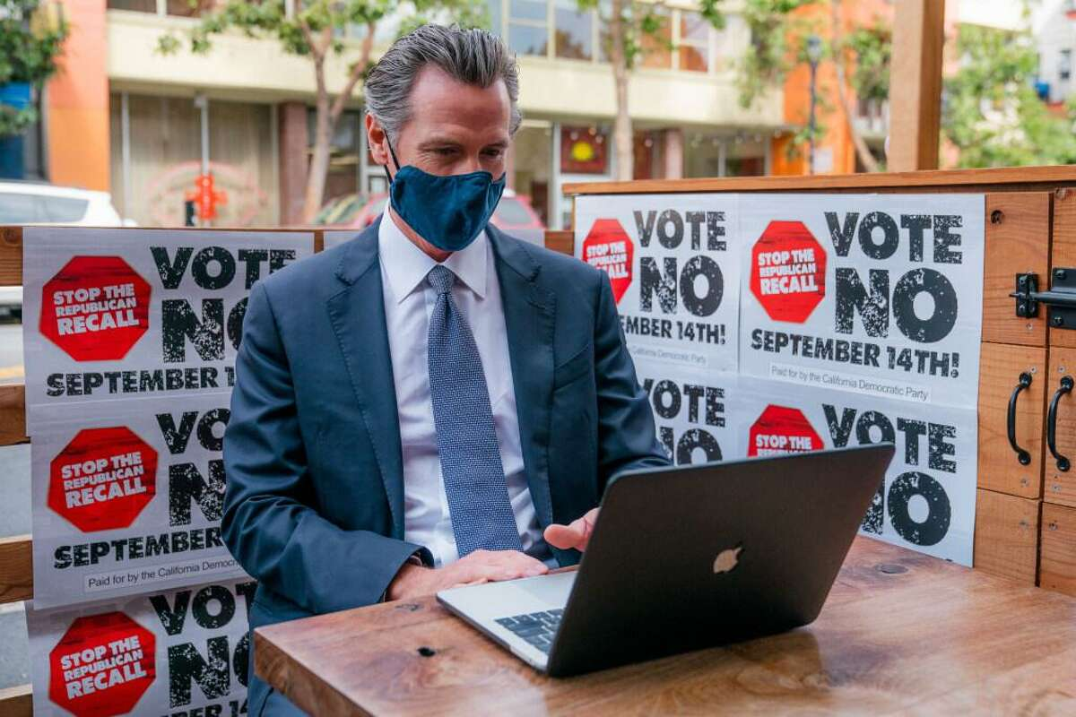 Gov. Gavin Newsom sends text messages to voters asking them to vote on in the recall election at Manny's cafe in San Francisco on Aug. 13.