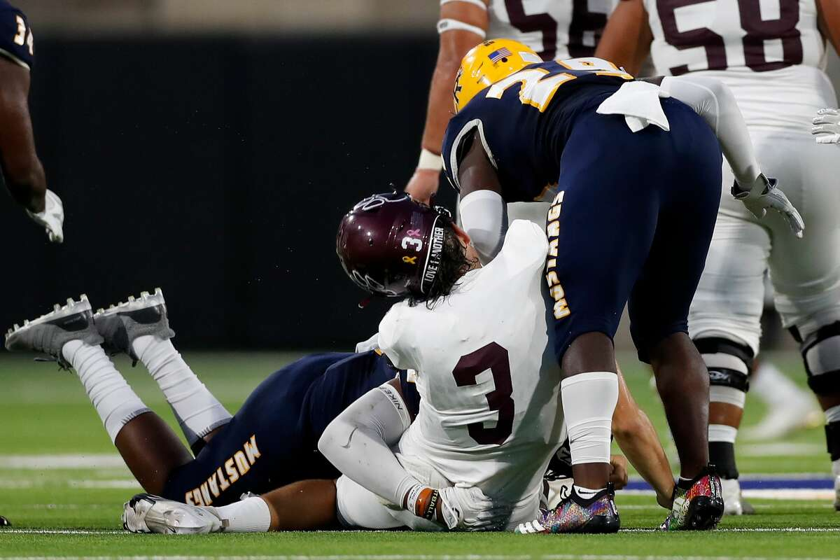 Cy-Fair Bobcats quarterback Trey Owens (3) is hit by Cypress Ranch Mustangs defensive lineman Ashton Porter (90) and linebacker Joseph White (34) during the first half of the high school football game between the Cy-Fair Bobcats and Cypress Ranch Mustangs at Cy-Fair FCU Stadium in Cypress, TX on Thursday, August 26, 2021.