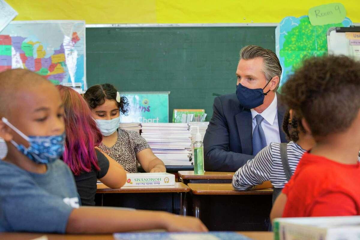 Gov. Gavin Newsom sits among students of a second-grade classroom at Carl B. Munck Elementary School in Oakland.
