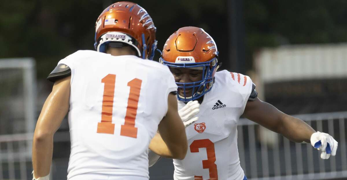 Grand Oaks running back Brandon High (3) gives a high five to tight end Christian Torres (11) after Torres scores a touchdown during the second quarter of a non-district football game against Aldine at Moorhead Stadium, Thursday, Aug. 26, 2021, in Conroe.