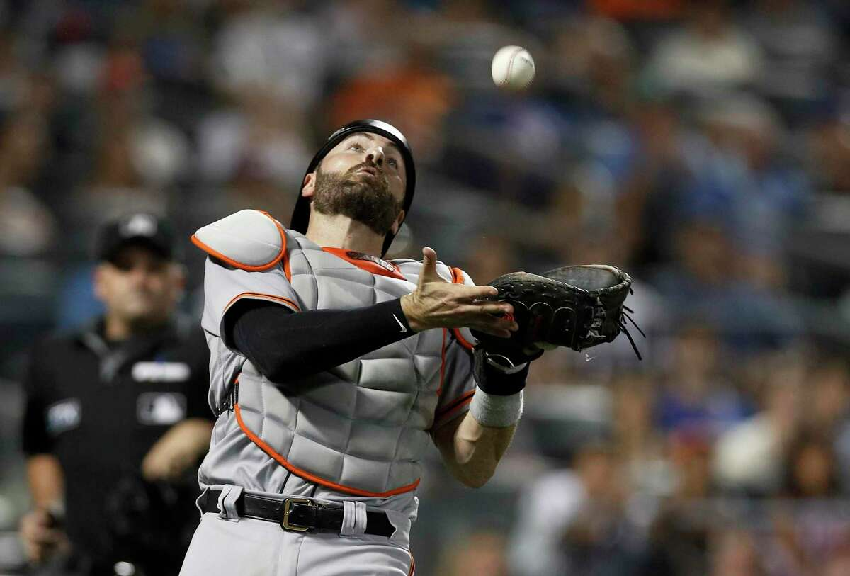NEW YORK, NEW YORK - AUGUST 25: Curt Casali #2 of the San Francisco Giants makes a catch for the final out of the eighth inning against the New York Mets at Citi Field on August 25, 2021 in New York City. (Photo by Jim McIsaac/Getty Images)