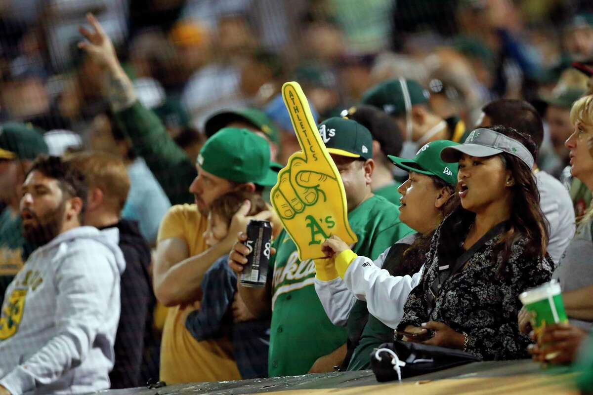 Oakland Athletics' fans cheer during 7th inning stretch while A's play New York Yankees during MLB game at Oakland Coliseum in Oakland, Calif., on Thursday, August 26, 2021.