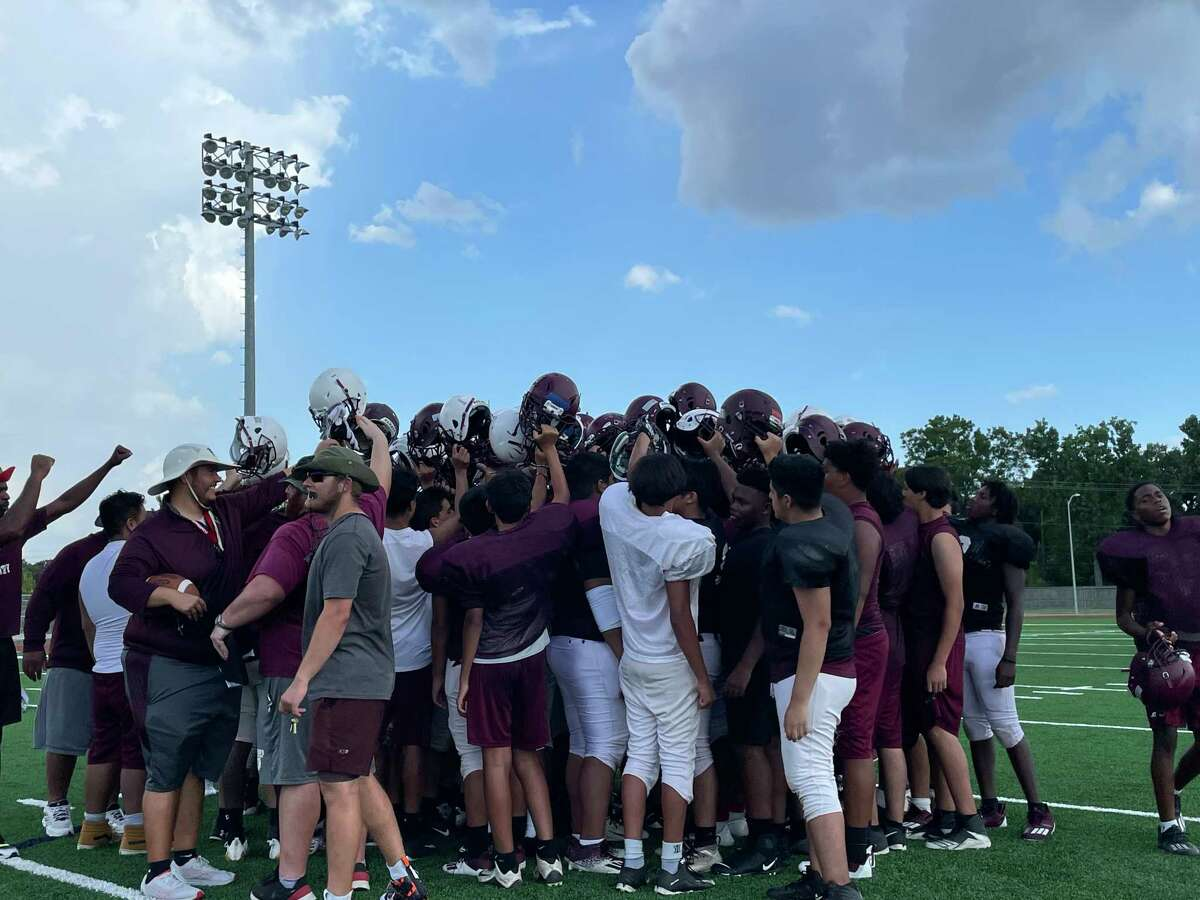 The Northbrook Raiders lift their helmets as they lean in to break at the end of football practice on Aug. 24.