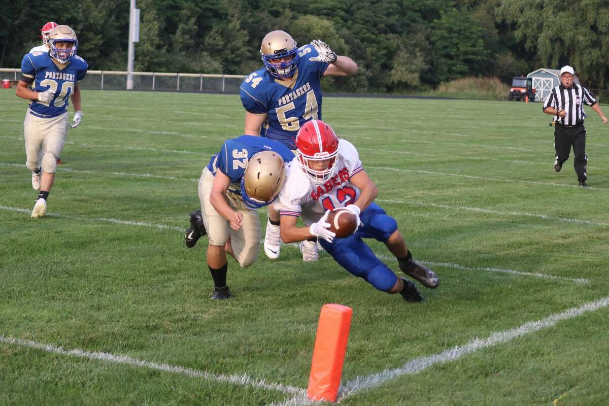 Manistee Catholic Central's Lee Pizana dives for the pylon as Onekama's Connor LeSarge tries to knock him out of bounds shy of the end zone.