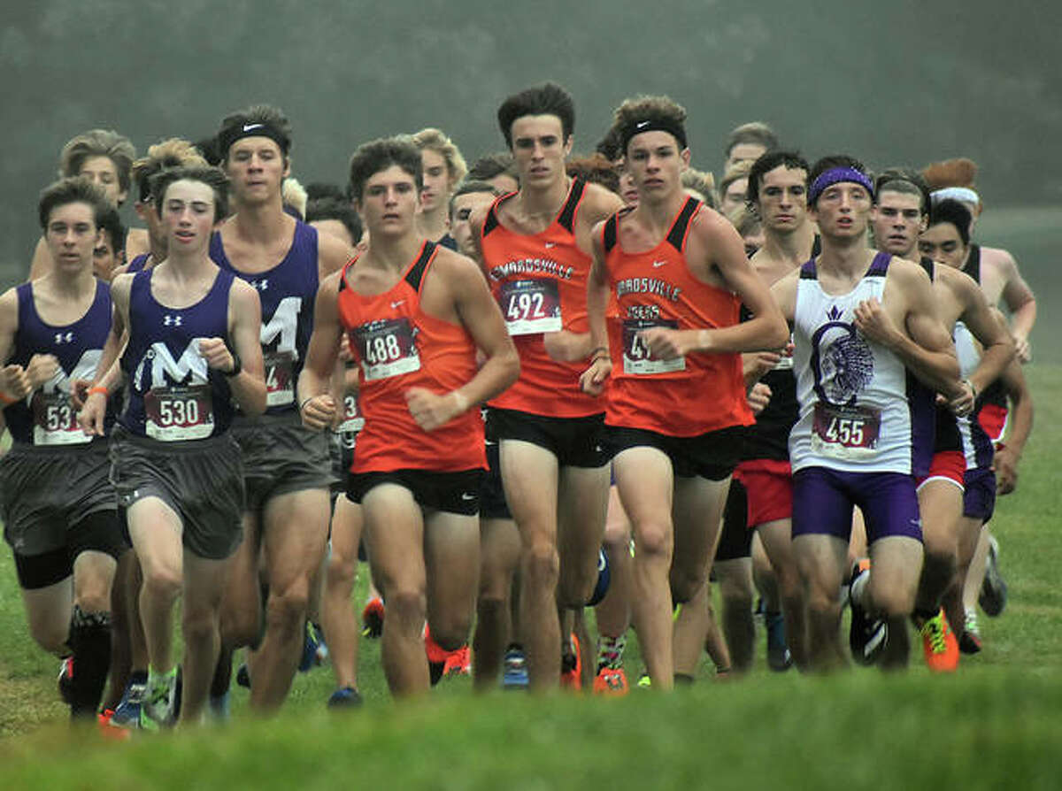 A pack of runners, including Edwardsville's Ryan Luitjohan, Ryan Watts and Geordan Patrylak, move up the hill shortly after the start of the Belleville West Invitational.