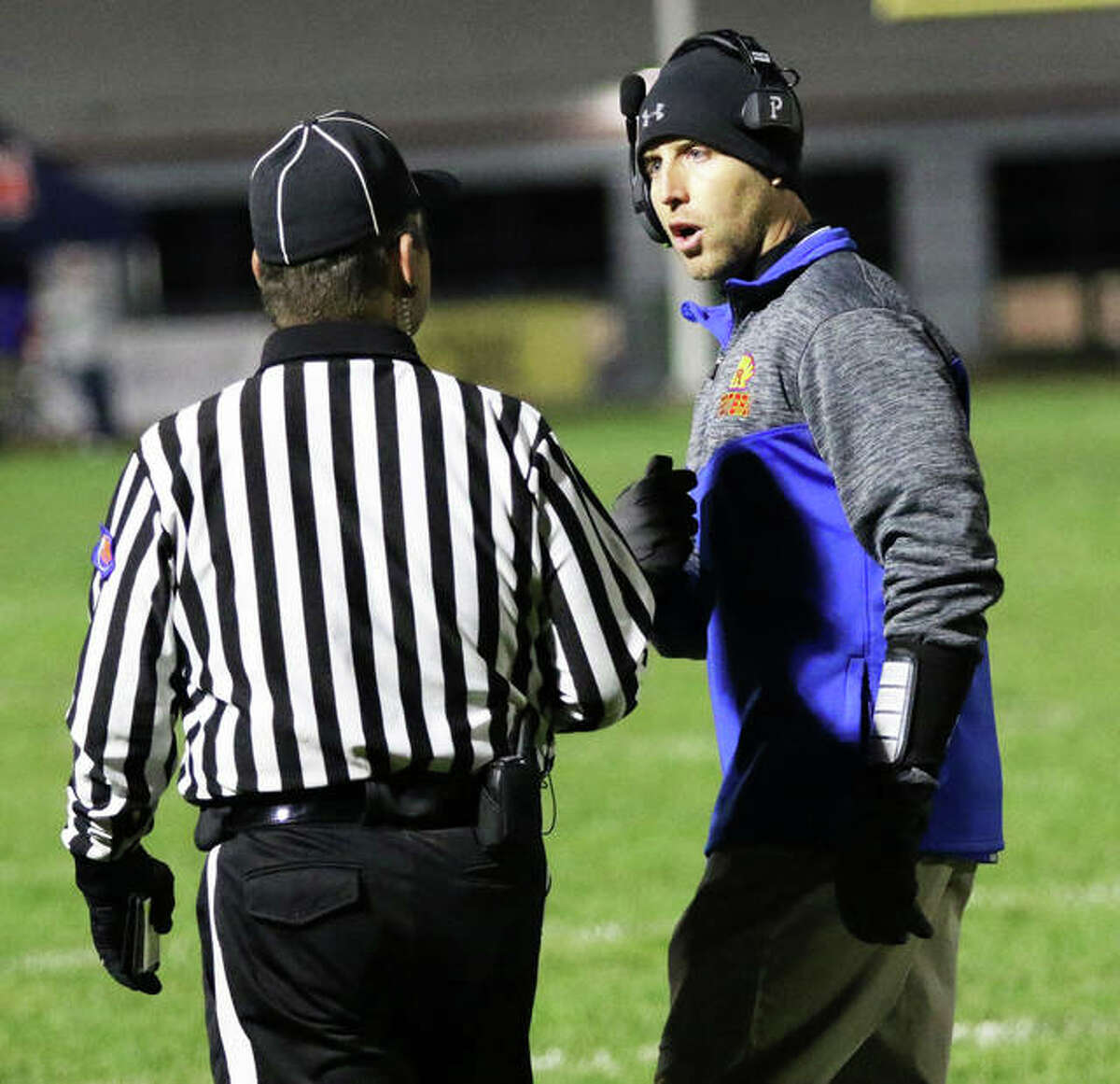 Roxana coach Wade DeVries (right) discusses a call with an official during a 2019 Shells' game against Gillespie at Charles Raich Field in Roxana.