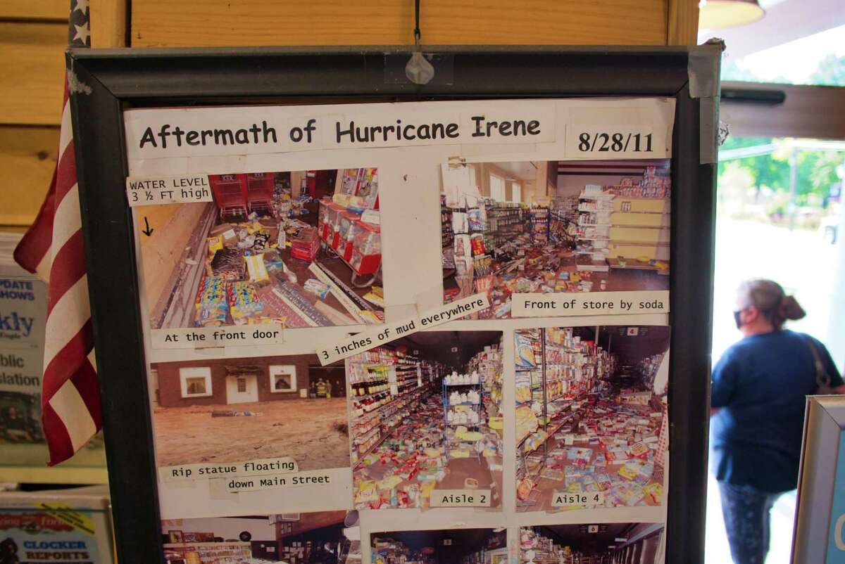 Photos from 2011 of the inside of the store Great American are seen hanging near the store's entrance on Thursday, Aug. 26, 2021, in Prattsville, N.Y. When the storm Irene hit the area the store was flooded with three feet of water.