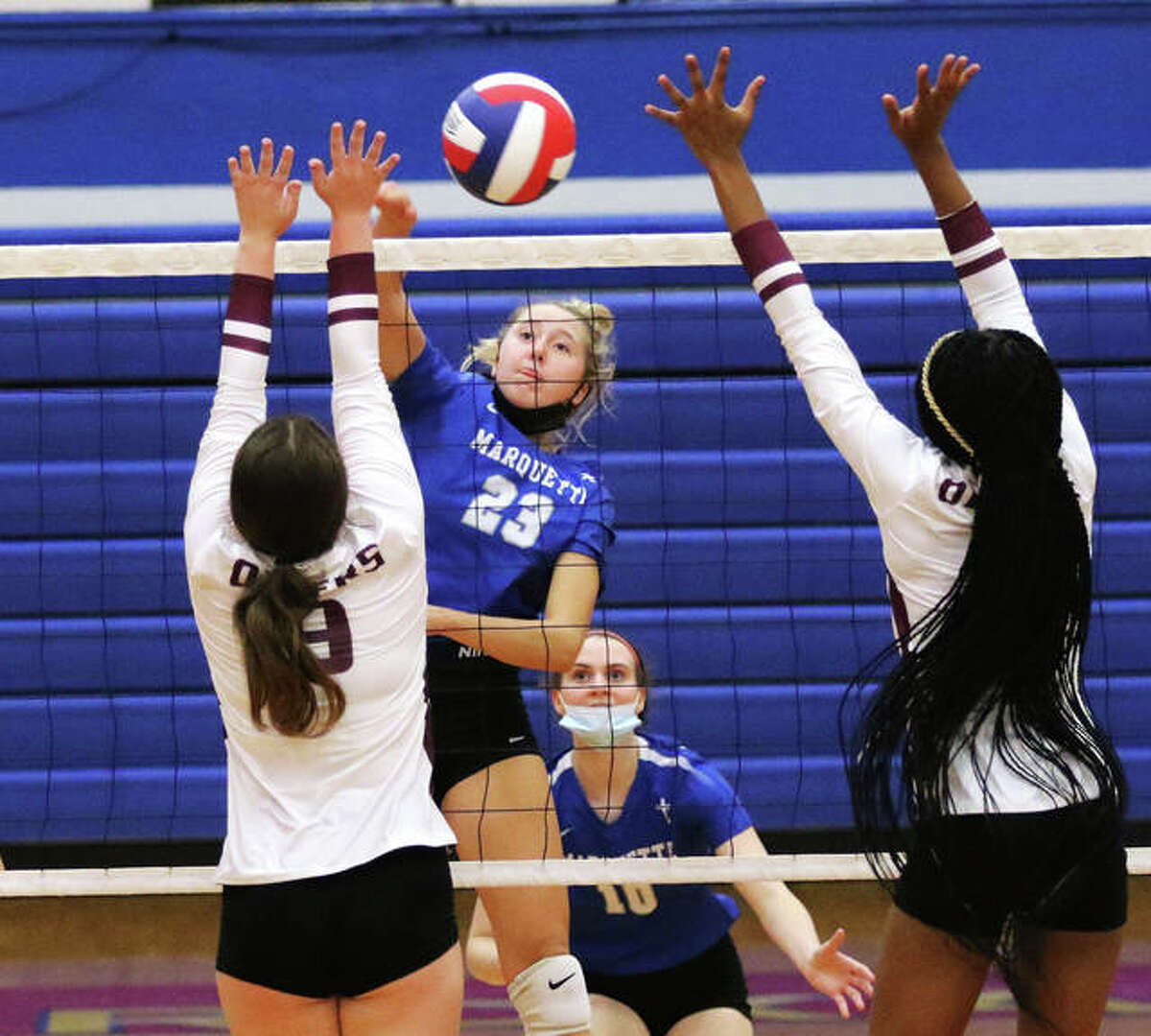 Marquette Catholic's Kylie Murray (23) hits between a double block put up by EA-WR during an Explorers win at the Roxana Tourney on Monday. The 4-0 Explorers opened at home Thursday night and swept Carrollton in two sets.