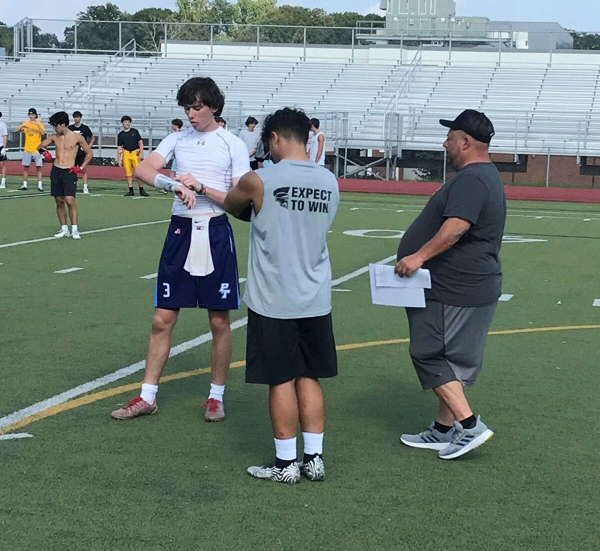 Amity coach Craig Bruno talks with Amity quarterback Patrick Coughlin at a practice, Wednesday, Aug. 25, 2021.