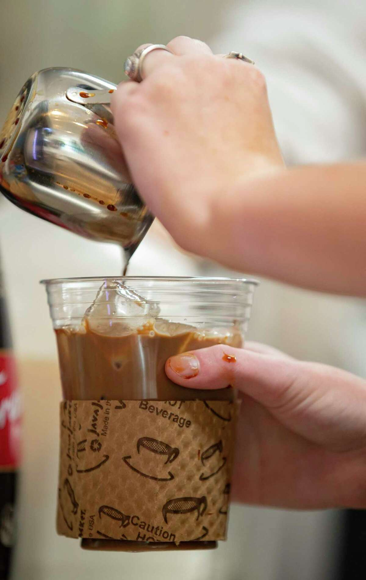Employees make an iced coffee drink during a practice day, Thursday, Aug. 26, 2021, at Belong Kitchen in Houston. Belong Kitchen, a grab-and-go outfit that employs young adults with intellectual and developmental disabilities, is getting ready to open up.