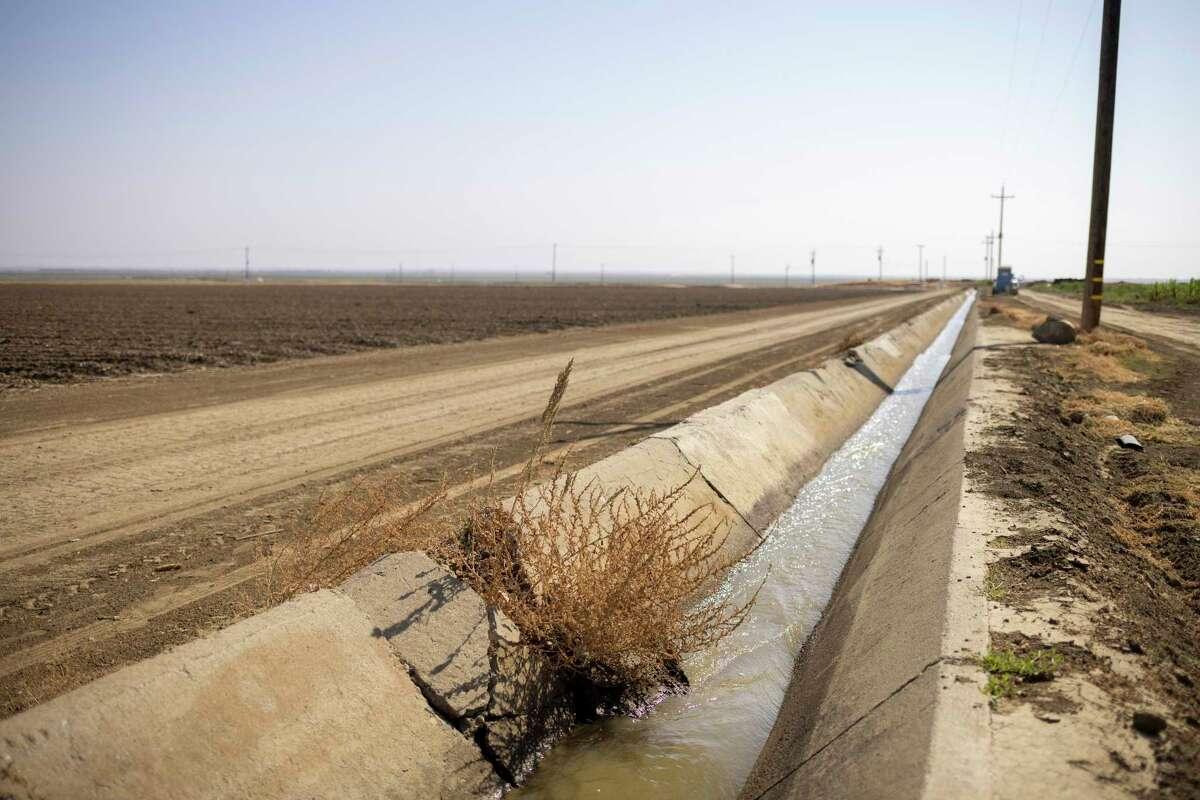 A trickle of water flows through an irrigation ditch in Firebaugh, Calif.