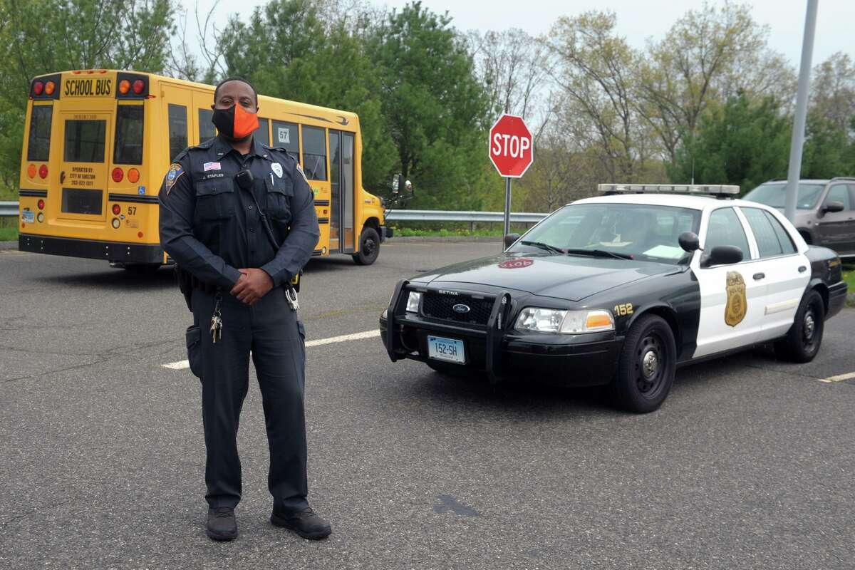 Shelton Police Officer John Staples poses in front of Perry Hill School, in Shelton, Conn. April 29, 2021.