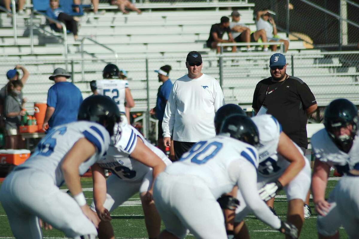 Friendswood football coach Robert Koopmann (left) watches the Mustangs during last week's scrimmage with Dawson.