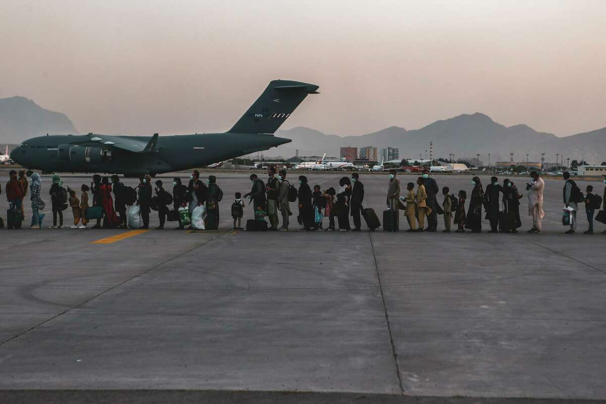 Evacuees wait to board a Boeing C-17 Globemaster III at Hamid Karzai International Airport in Kabul, Afghanistan, last week. What ghosts travel with them?