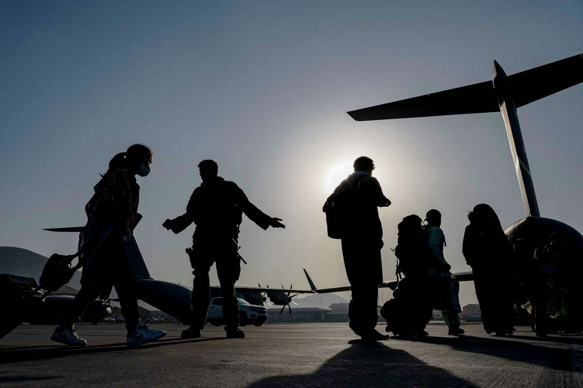 A U.S. Air Force Airman guide evacuees aboard a U.S. Air Force C-17 Globemaster III at Hamid Karzai International Airport in Kabul, Afghanistan. Memories from the war will ride along, too.