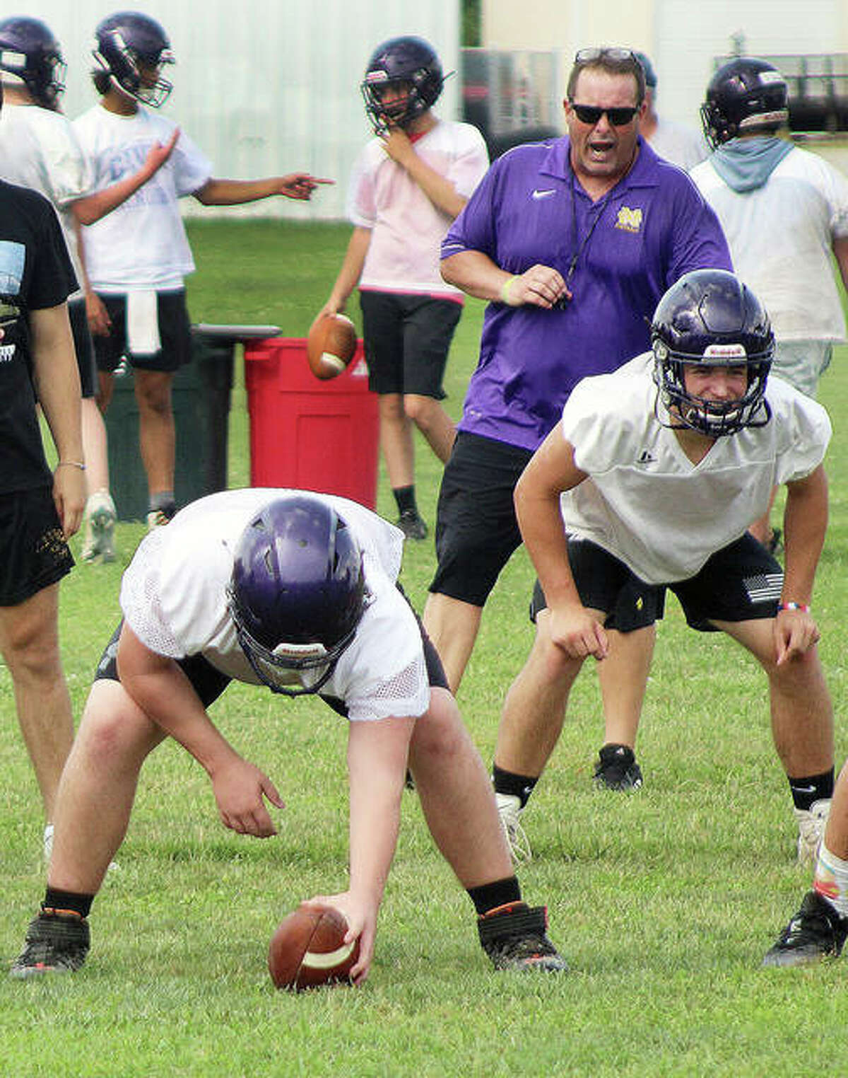 Civic Memorial head coach Mike Parmentier shouts out signals during a preseason drill. The Eagles open their season Aug. 27 against Marquette Catholic High at Public School Stadium.