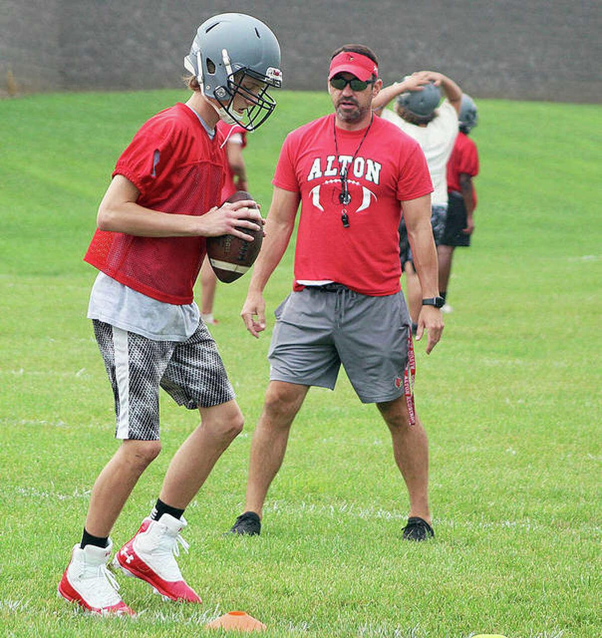 Alton coach Eric Dickerson watches freshman quarterback Aaron Humm drop back during a preseason practice at Alton High School.
