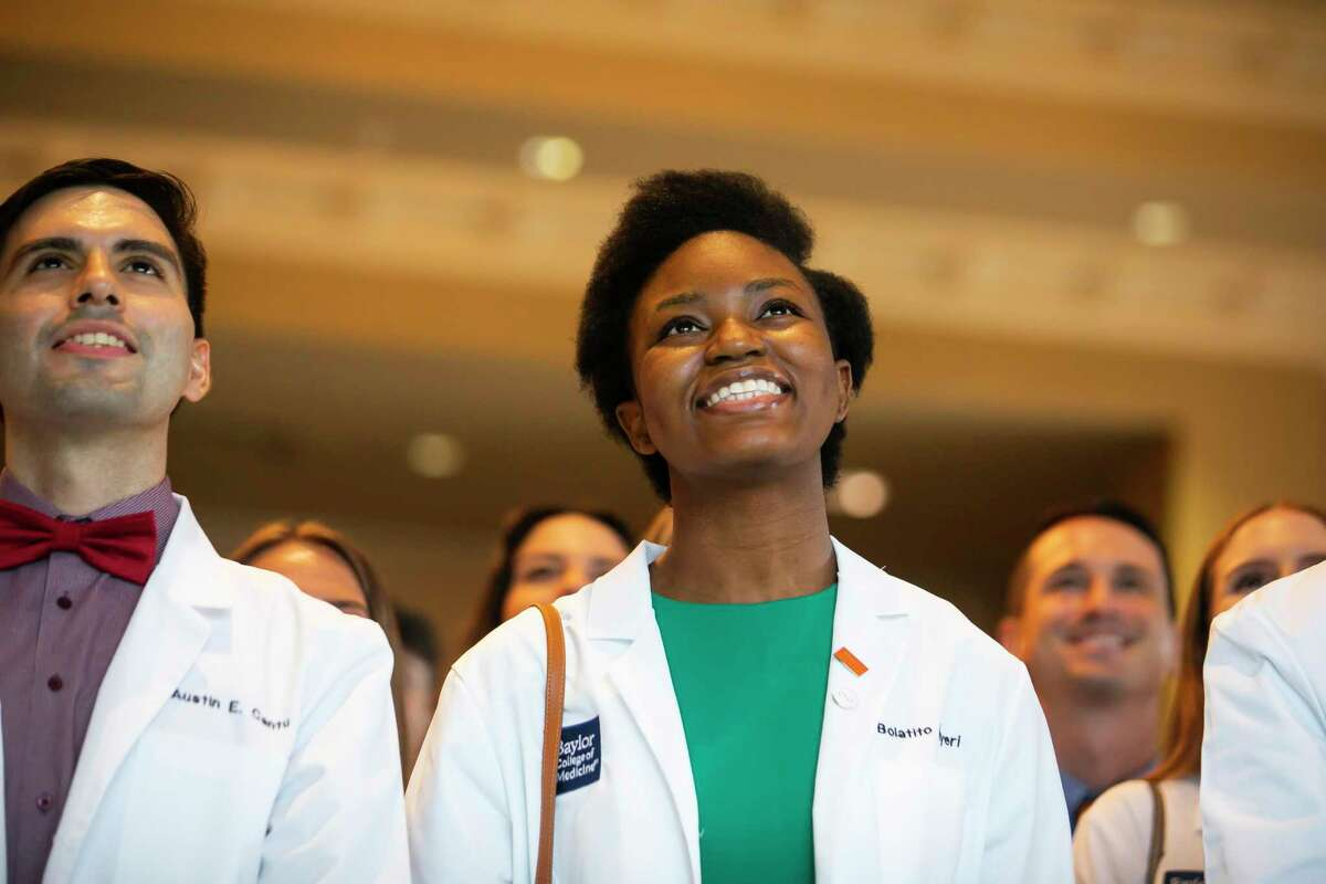 Baylor College of Medicine student Bolatito Adeyeri briefly takes off her mask for a group photo after her white coat ceremony at the Bayou City Event Center on Friday, Aug. 13, 2021.