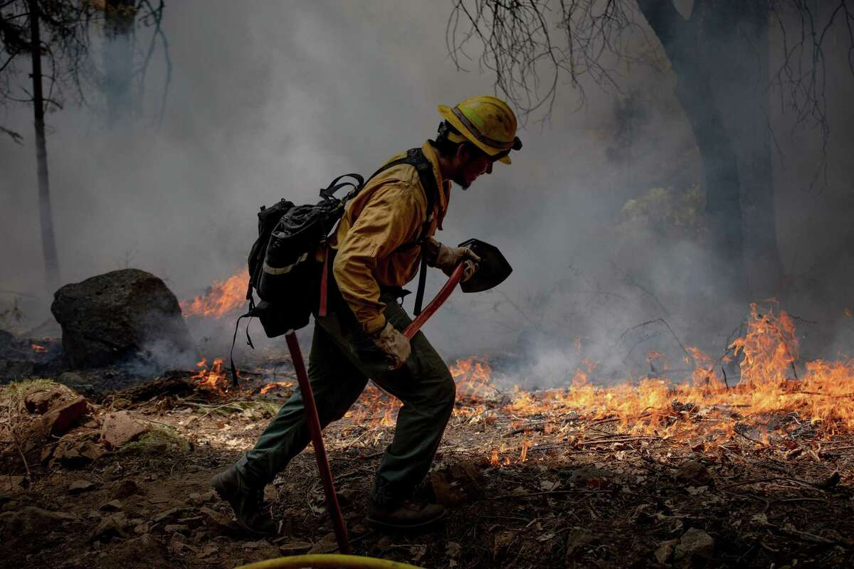 A firefighter at the Dixie Fire near Greenville, Calif., Aug. 9, 2021. (Christian Monterrosa/The New York Times)