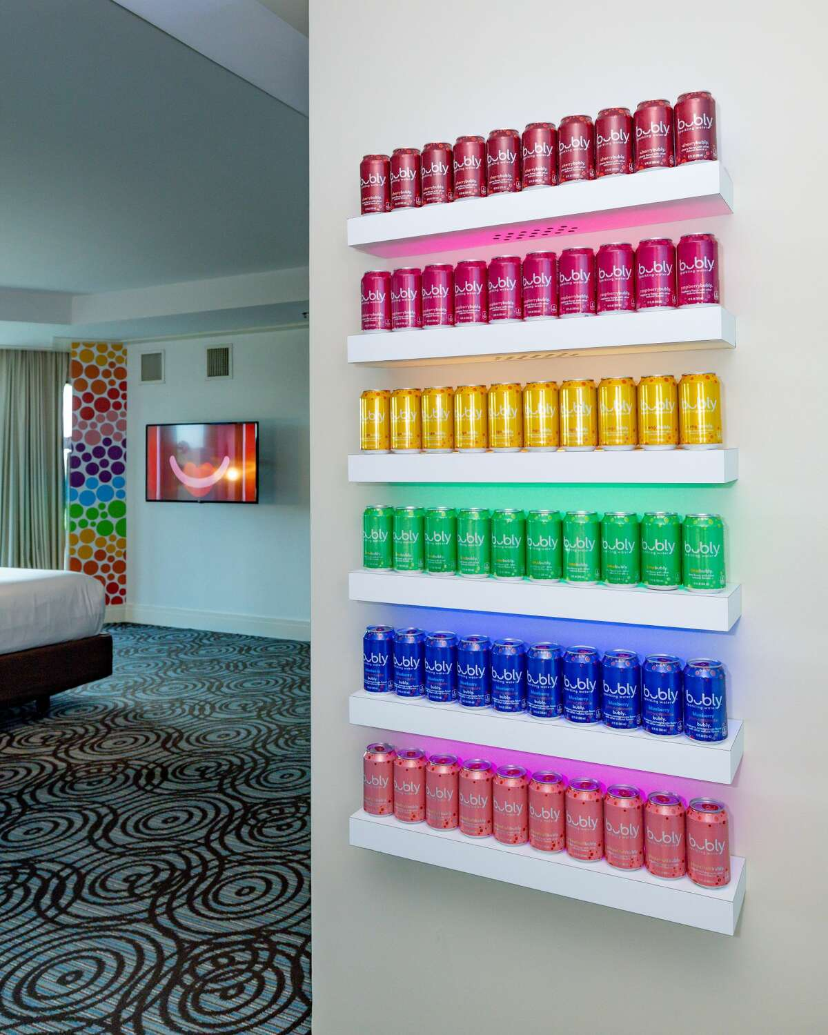 Interactive installations include an Instagram-ready Magic Mirror, a custom-designed centerpiece rainbow couch in the shape of the beverage company's signature smile logo, an in-suite bar with bubly products and a light-up rainbow wall made from cans.