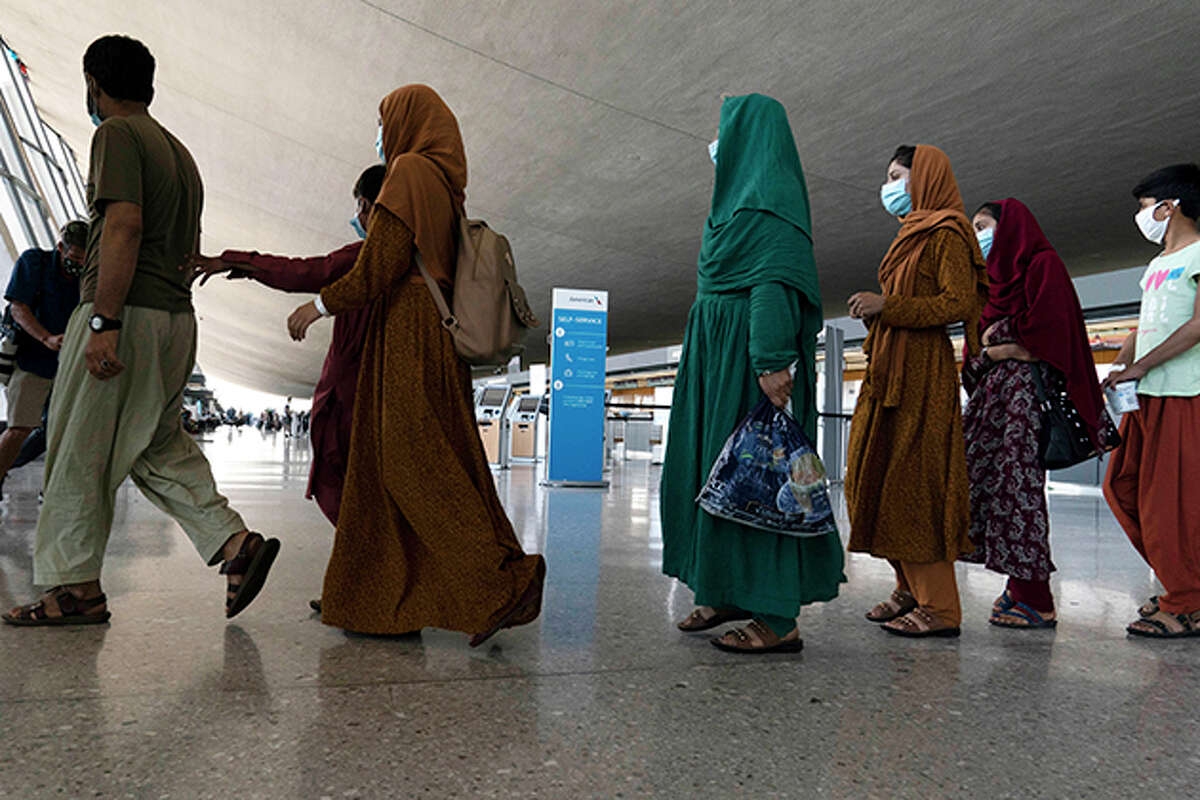 Families evacuated from Kabul, Afghanistan, walk through the terminal before boarding a bus after they arrived at Washington Dulles International Airport, in Chantilly, Va., on Friday, Aug. 27.