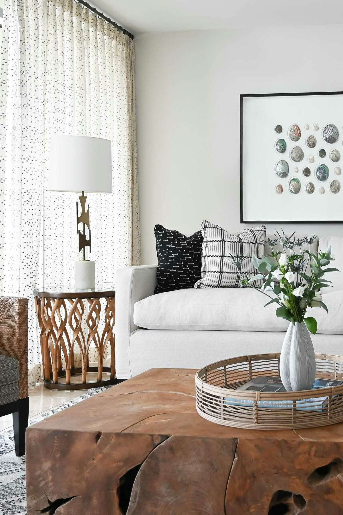 A burled wood coffee table and cane side table bring organic elements to the living room.