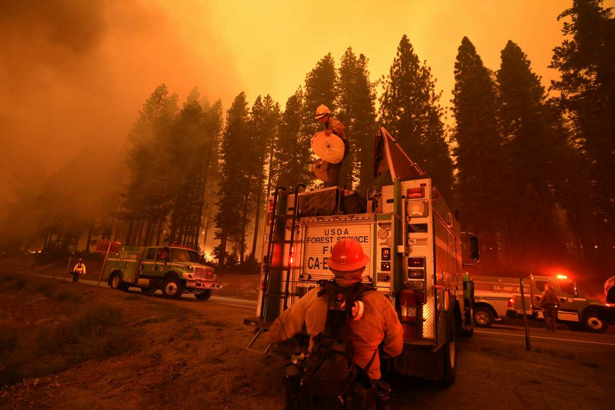 Firefighters respond to Caldor Fire as it shows a significant fire activity along US Highway 50 near Kyburzon Aug. 26, 2021.