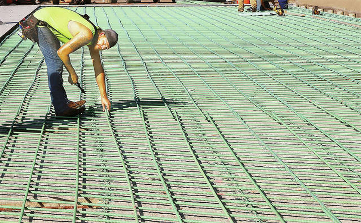 A construction worker ties reinforcing rods together to prepare the westbound lanes of the Illinois 140 bridge over Wood River Creek in Alton for a new concrete deck.