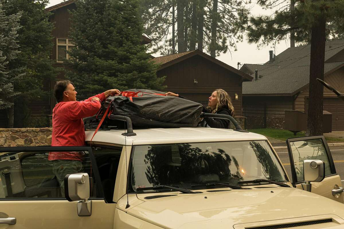 Don Boatwright helps his friend RaShell Holland pack her FJ Cruiser in South Lake Tahoe. Holland is leaving town with her 17-year-old son to escape the wildfire smoke. She has lived in the area since 1995 and says this is the worst air quality she has experienced. She said the air quality in her bedroom last night reached 555.