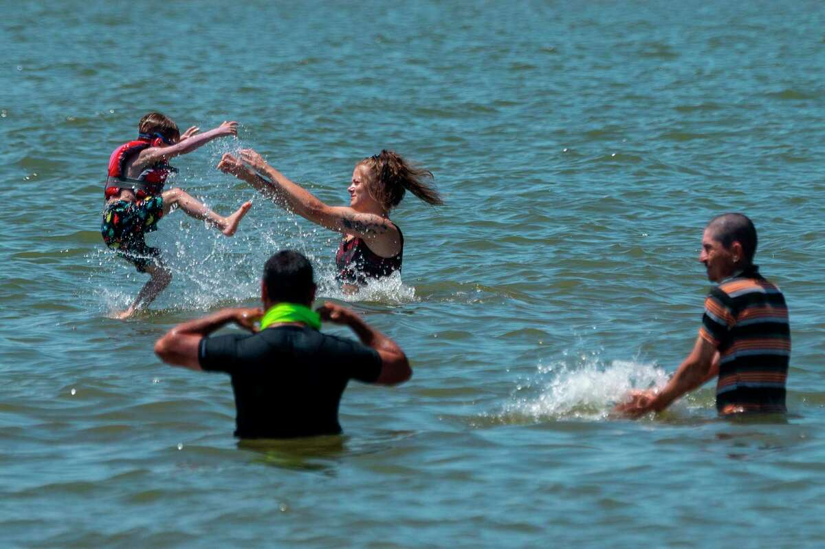 People try to escape the heat in the Chesapeake Bay at Sandy Point State Park in Annapolis, Maryland. Heat indices in Big Rapids this weekend could reach the high 90s. (Photo by JIM WATSON/AFP via Getty Images)