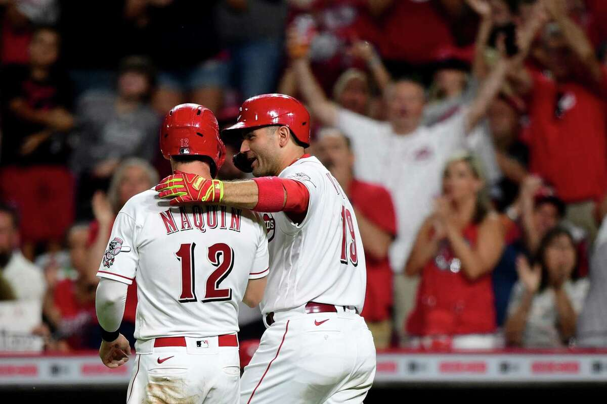 CINCINNATI, OHIO - AUGUST 21: Joey Votto #19 hugs teammate Tyler Naquin #12 of the Cincinnati Reds after Naquin slid into home base to score in the eighth inning during their game against the Miami Marlins at Great American Ball Park on August 21, 2021 in Cincinnati, Ohio. (Photo by Emilee Chinn/Getty Images)