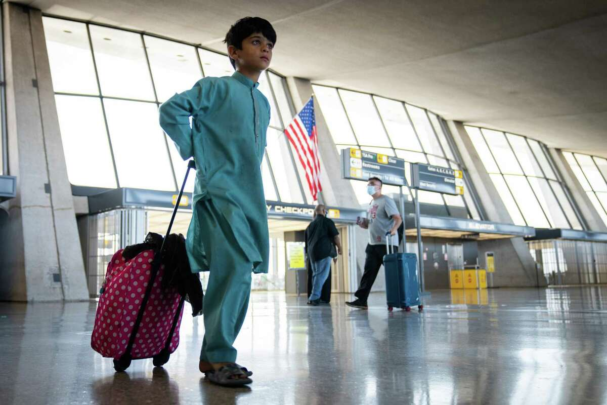 A young Afghan refugee walks through Dulles International Airport in Dulles, Va., Thursday, Aug. 26, 2021, with an American flag in the background, before bussing to a processing center. The Pentagon flew out 13,400 people from Hamid Karzai International Airport in Kabul in the past 24 hours, military officials said on Thursday, a sharp decline from the past few days largely because receiving bases in the Middle East are again filling up. (Sarahbeth Maney/The New York Times)