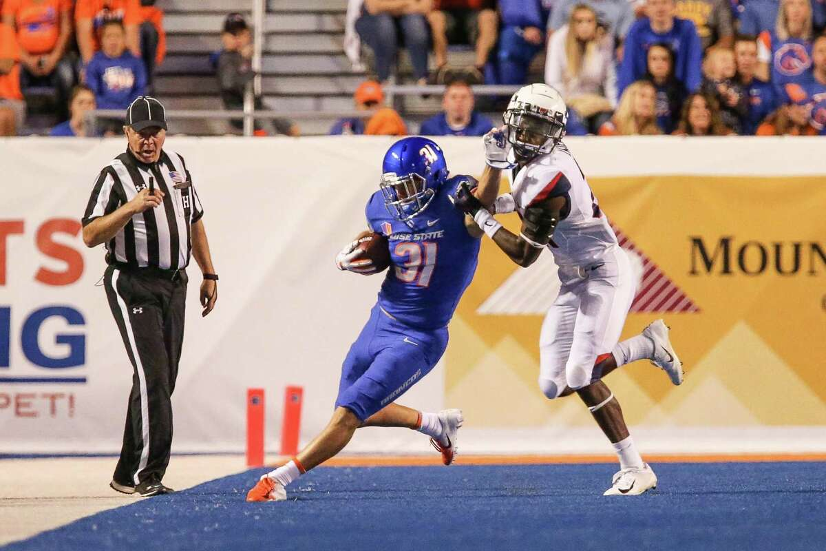 Boise State's Skyler Seibold pushes off the tackle attempt of UConn defensive back Jeremy Lucien during a game in 2018.