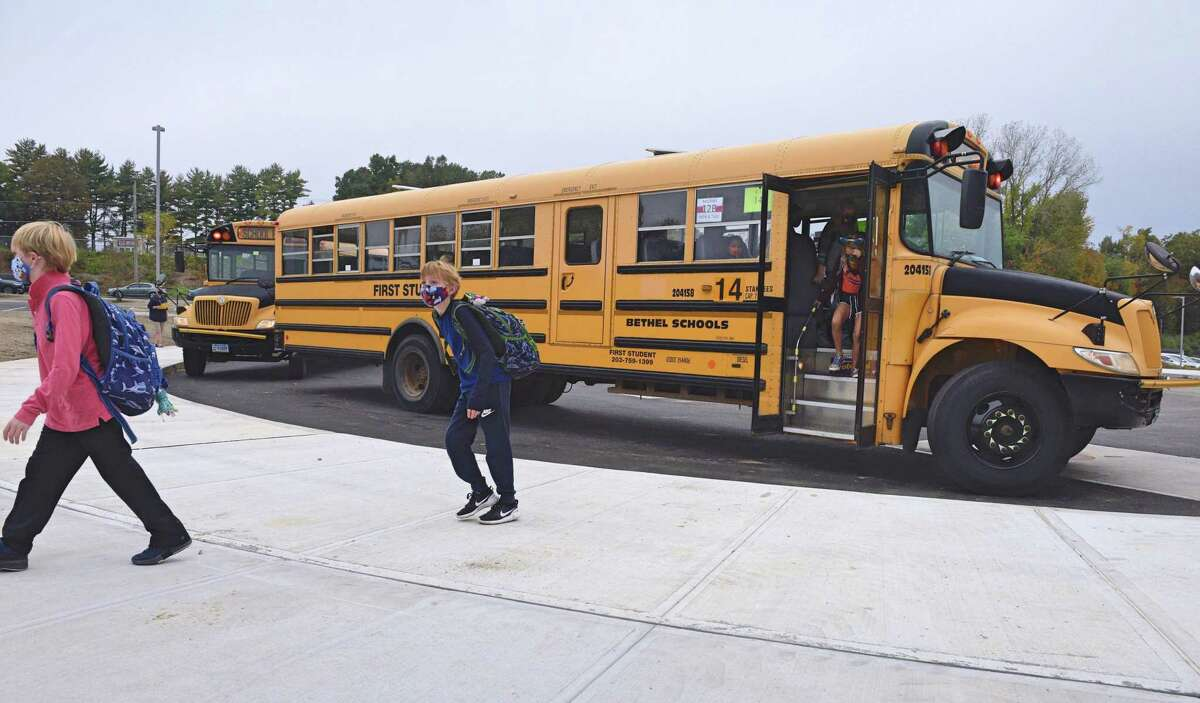 Mask-wearing students get off a bus at the Ralph M. T. Johnson Elementary School in Bethel, Conn., in September 2020.