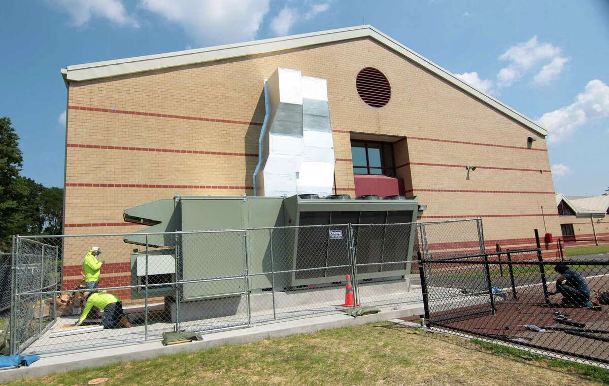 """Workers from KMK Insulation of North Haven, finish working on the new DOAS system, or """"dedicated outdoor air system,"""" at Westover Elementary School in Stamford, Conn., on Friday August 27, 2021."""