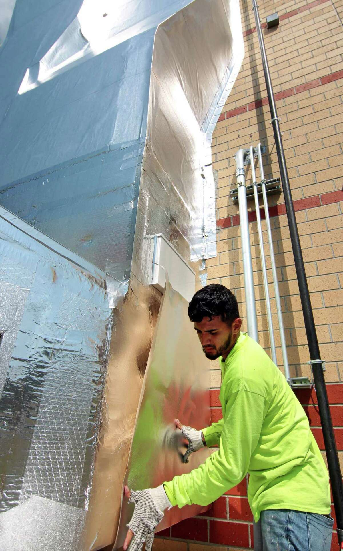 """Brian Giraldo from KMK Insulation of North Haven, finishes working on the new DOAS system, or """"dedicated outdoor air system,"""" at Westover Elementary School in Stamford, Conn., on Friday August 27, 2021."""
