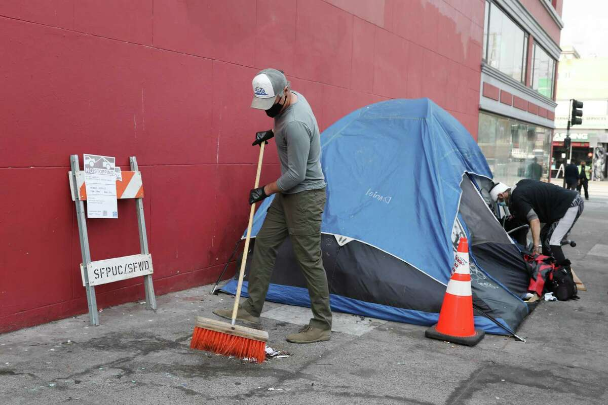 Governor Newsom sweeps outside Ariel Fortuna's tent as Fortuna clears some belongings on 19th Street, August 27, 2021 in San Francisco.