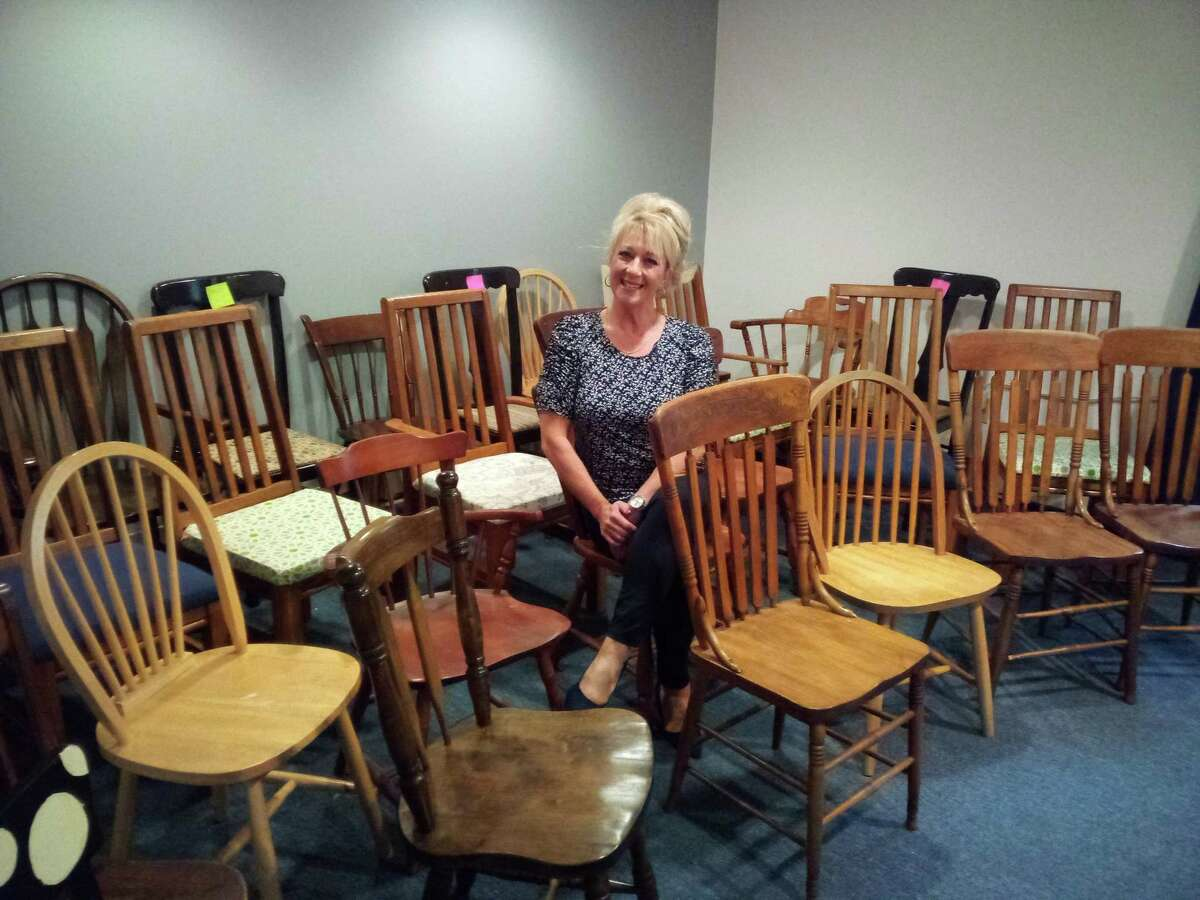 """Friendly Hands Food Bank's next fundraiser is """"A Seat at Our Table,"""" with a live auction of wooden chairs that will be transformed into works of art by November. Artists are still wanted to take a chair home and recreate it for the food bank. Pictured is Executive Director Karen Thomas with the collection of donated chairs."""