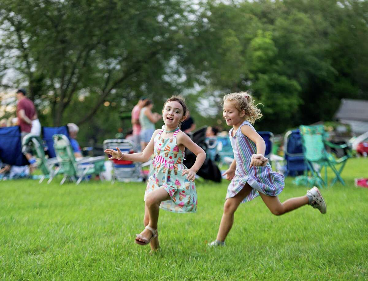 Vienna Eriksen and Amelia Ruggiero play Duck, Duck, Goose at Ambler Farm's Sayonara to Summer concert with Grateful Dead tribute band, Bear's Choice, on Saturday, Aug. 21, 2021, in Wilton, Connecticut.