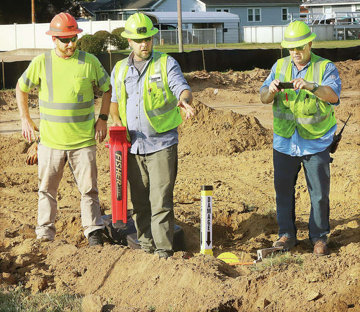 Three workers from the Ameren Gas Division mark the spot of a gas leak Friday morning near the corner of Madison and Central avenues in Wood River. The leak was caused by groundwork for an extension of the parking lot of the adjacent Petro Mart convienience store. No injuries were reported.