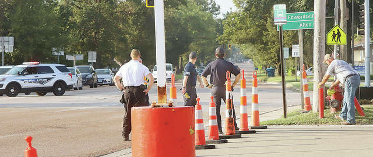 Wood River firefighters watch the area of the gas leak Friday morning at the intersection of Illinois 111 and 143 while Roxana Police, left, block traffic.
