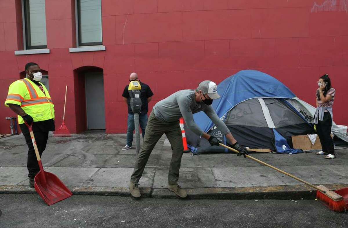 Governor Gavin Newsom (center) works with members of the the Department of Public Works Hot Spot team as they sweep at a homeless encampment on 19th Street on Friday, August 27, 2021 in San Francisco, Calif.