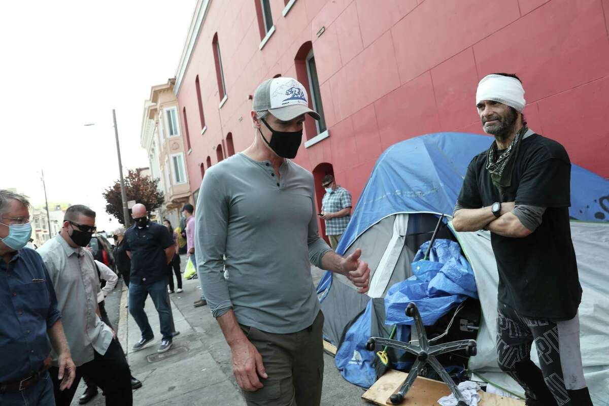 Governor Gavin Newsom (l to r) talks with Ariel Fortuna outside the tent Fortuna lives in as he visits a homeless encampment on 19th Street on Friday, August 27, 2021 in San Francisco, Calif.