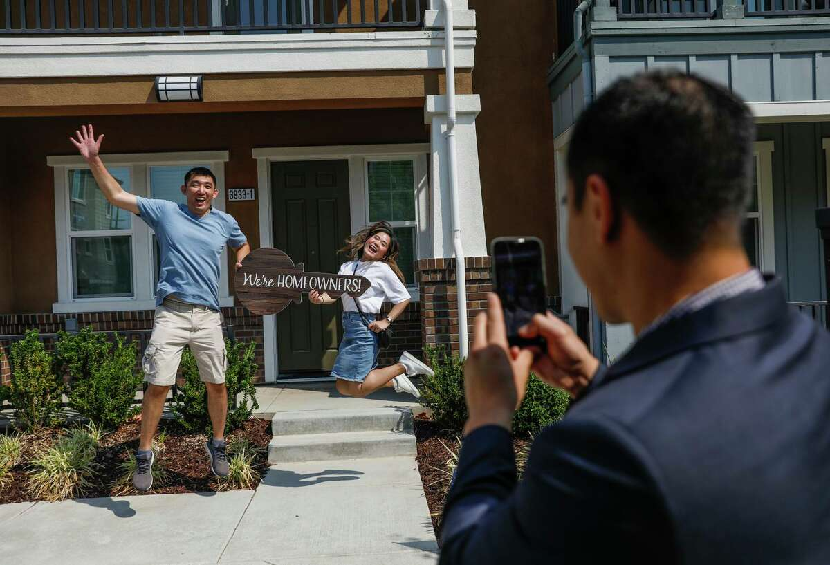 """Realtor Scott Nguyen (right) photographs new homeowners Martin Wong (left) and Jann Ton at their newly purchased home. Nguyen carries a """"We're Homeowners!"""" sign to every home inspection and takes a photograph for clients to upload to social media."""