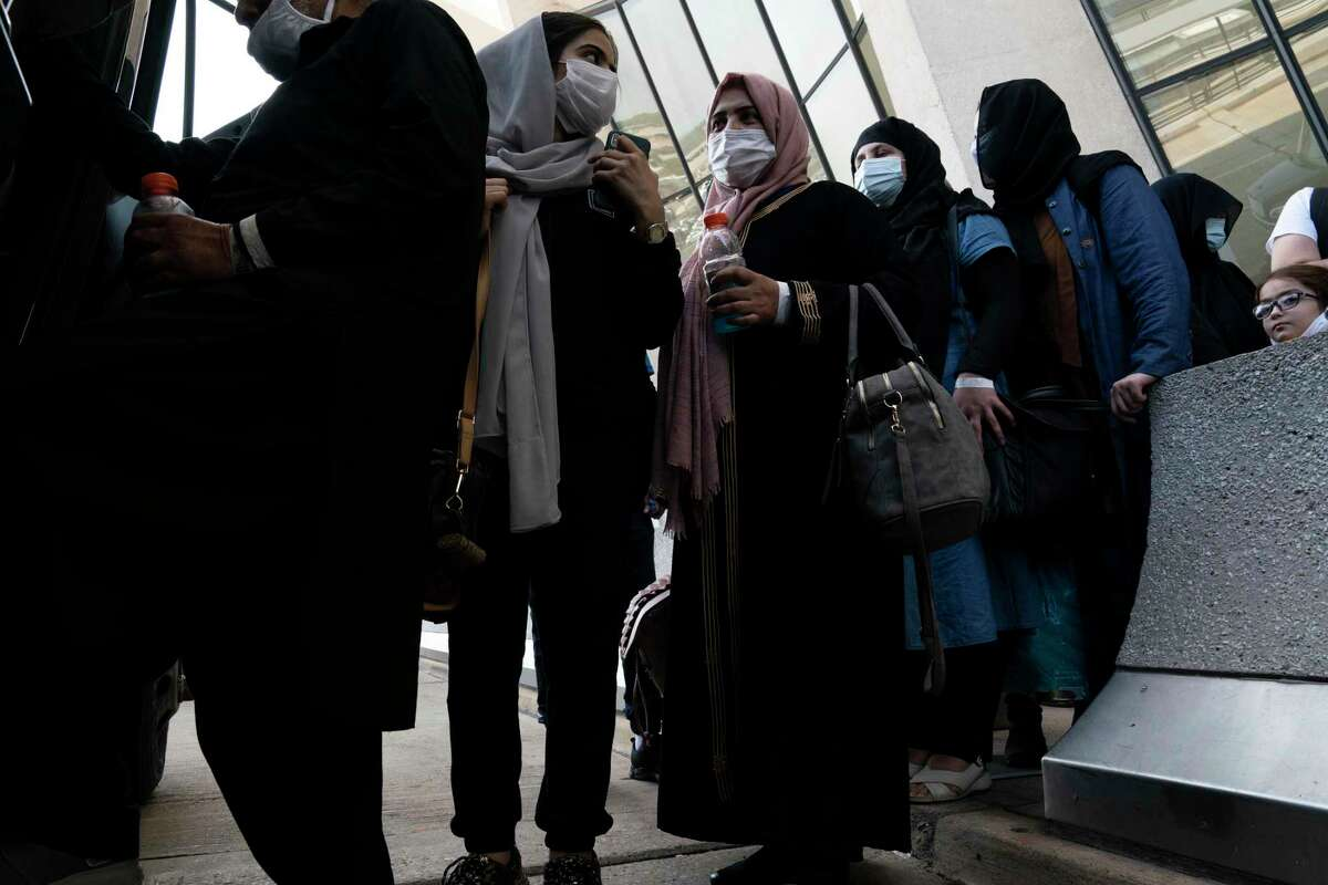 Families evacuated from Kabul, Afghanistan, wait before boarding a bus at Washington Dulles International Airport, in Chantilly, Va., on Friday.