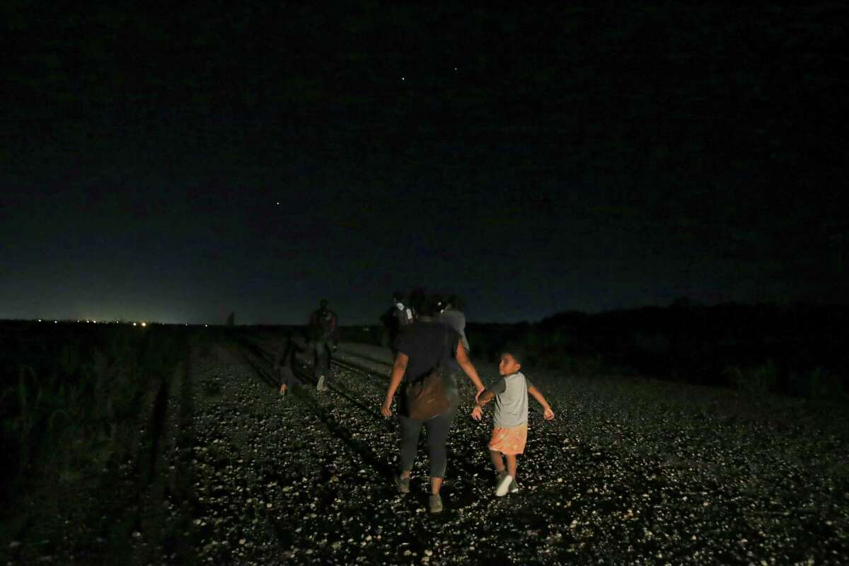 Migrant families walk to a Border Patrol processing area under the guidance from La Joya police officers.