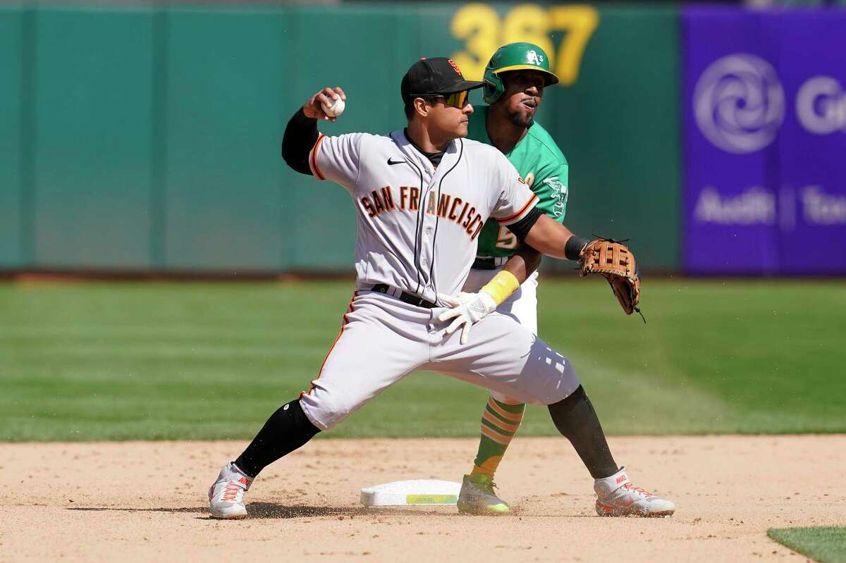 San Francisco Giants' Donovan Solano, foreground, in front of Oakland Athletics' Tony Kemp during a baseball game in Oakland, Calif., Sunday, Aug. 22, 2021. (AP Photo/Jeff Chiu)