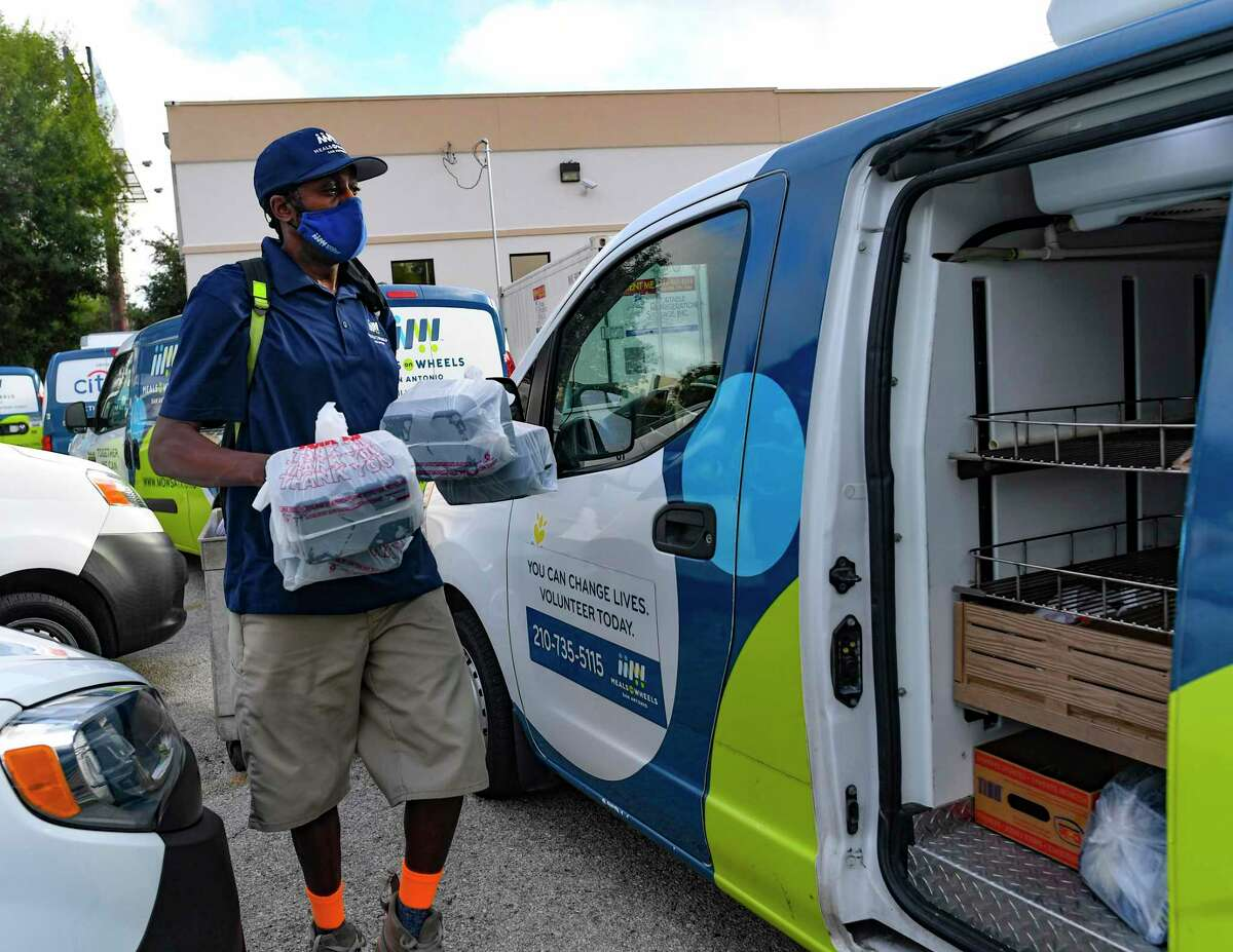 Marc Hillary wheels a cartful of meals into the delivery vehicle parking area at Meals on Wheels' facility on Loop 410 at Callaghan Road on Aug. 10, 2021.