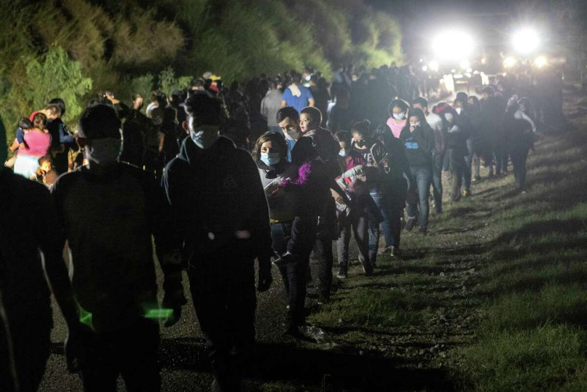 Immigrants walk toward buses that will travel to a processing center from a Border Patrol checkpoint in Roma on Aug. 14.