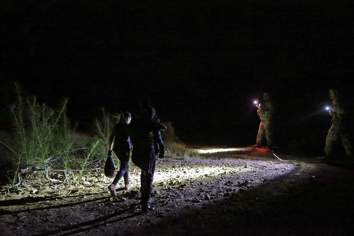 Migrants walk towards National Guardsmen after they were smuggled across the Rio Grande into the U.S. at a point in Roma, Texas, Wednesday, Aug. 11, 2021. Three different smuggling operations were seen crossing mostly Central American migrants at the site. One of the smugglers claimed he had around 180 people to cross.